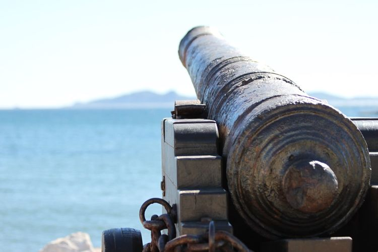 Close-up of old cannon at observation point by sea against sky
