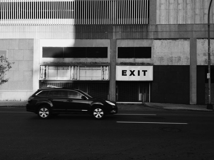 Car on street against exit sign on building