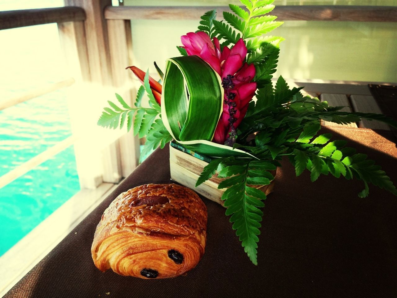 Close-up of croissant and flower pot on table in boat