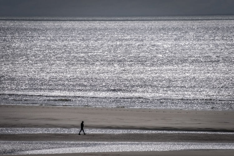Distant view of man walking at beach