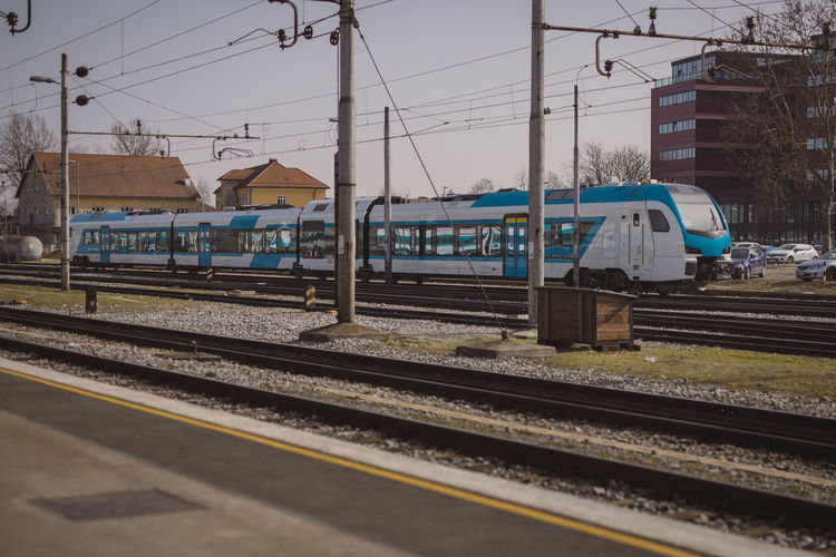 Train at railroad station in city against sky