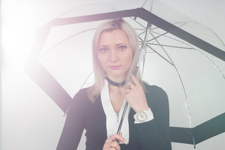 Portrait Of Young Woman Holding Umbrella While Standing Against White Background