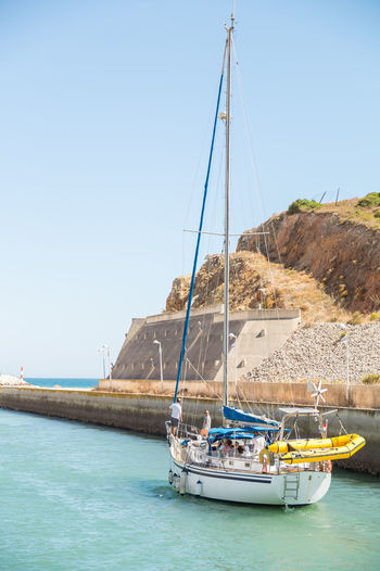 Sailboats moored on sea against clear sky