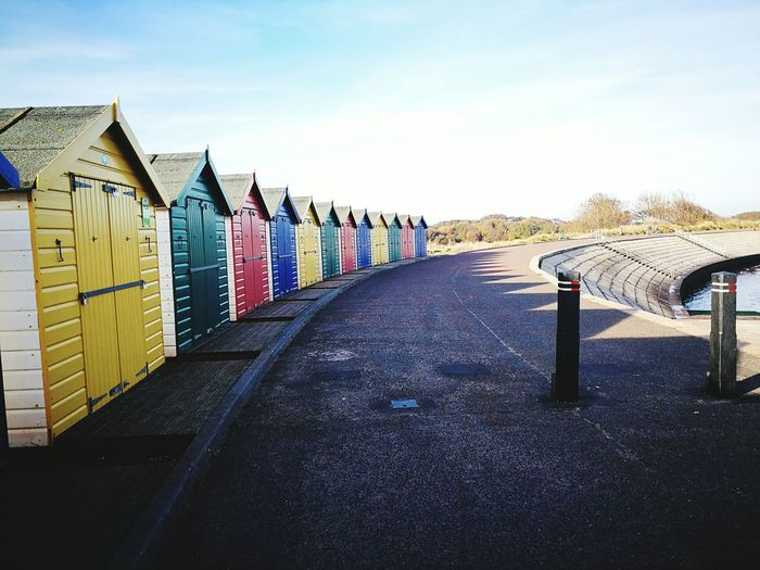 Colorful Beach Houses In A Row Along Empty Road