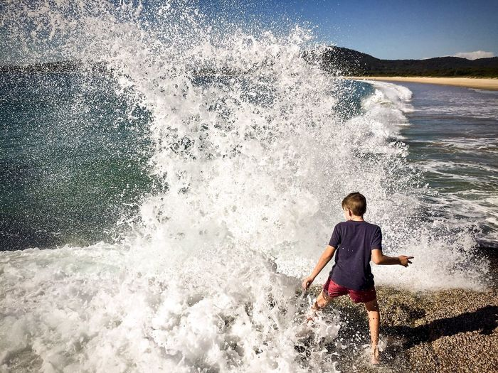 Rear view of boy standing by splashing water at beach
