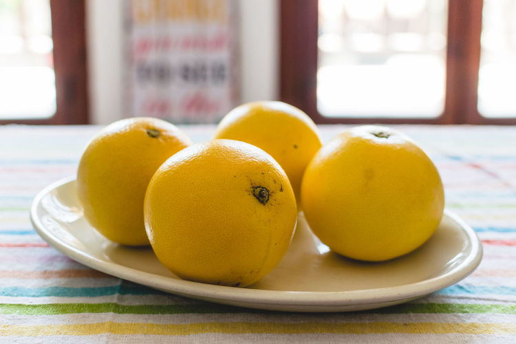 Citrus Fruit Close-up Day Focus On Foreground Food Food And Drink Freshness Fruit Grapefruit Healthy Eating Indoors  No People Plate Table Window Yellow
