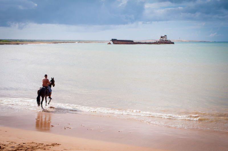 Shirtless man riding horse at beach against cloudy sky during sunny day