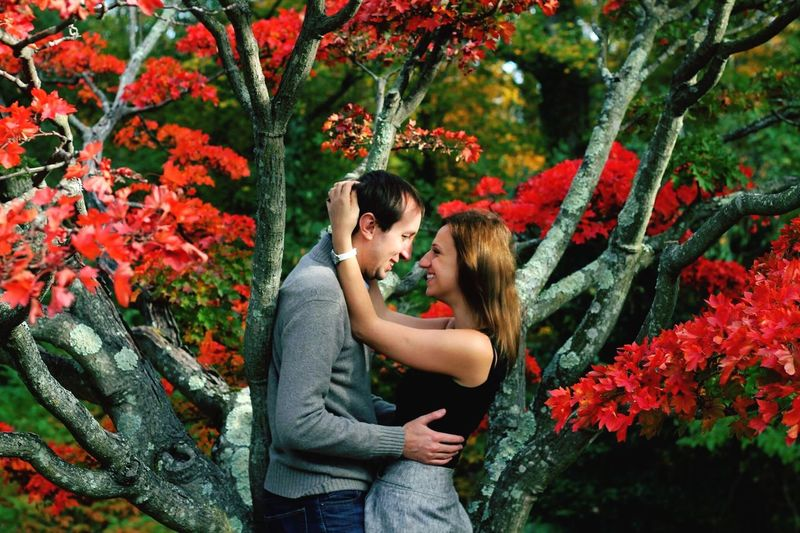 Young Woman With Man And Red Flowers Against Trees