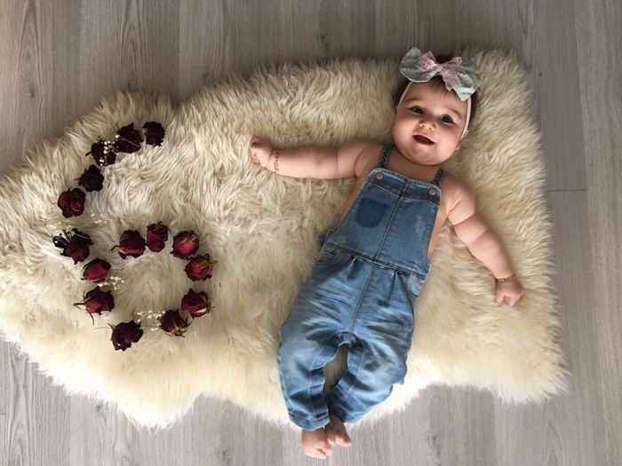 Directly above shot of baby girl lying by roses arranged in number 6 on rug