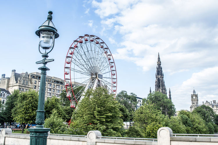 Ferris Wheel By Historic Scott Monument In City Against Sky
