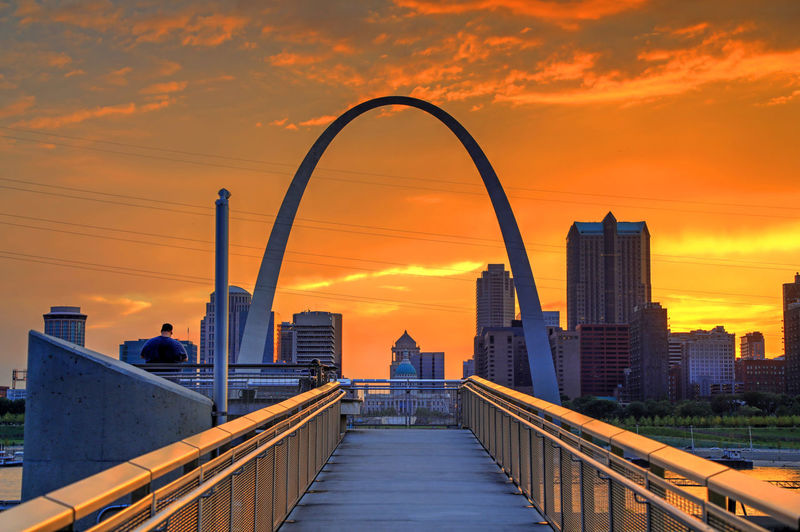 View of bridge and buildings against orange sky during sunset