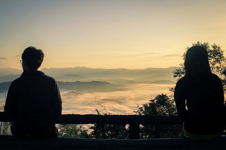 Soft focus, Back view Silhouette,young couple standing and look forward to the sun rises in the morning on the mountain with beautiful sky background. Romantic moment ,Couple,Valentine concept. Sky Sunset Real People Beauty In Nature Leisure Activity Rear View Men Lifestyles Scenics - Nature Mountain Nature People Looking At View Tranquility Tranquil Scene Orange Color Three Quarter Length Non-urban Scene Standing Outdoors Fog person Travel Landscape Tourism Nature Hiking Beautiful Adventure Peak Top Looking Looking Away Sun Tourist Trip Trekking Sunrise Vacations Summer Inspiration Hills Clouds Destinations Thinking Panoramic Traveler Sitting Foggy Foggy Morning