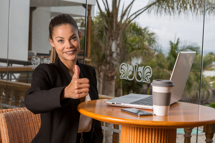 Trendy young woman holding thumb up and smiling at camera sitting at table with laptop and coffee in resort cafe Achievement Business Modern Woman Cafeteria Chair Communication Computer Connection Holding Laptop One Person Portrait Resort Seat Sitting Smiling Success Table Technology Thunderstorm Travel Destinations Using Laptop Wireless Technology Young Women