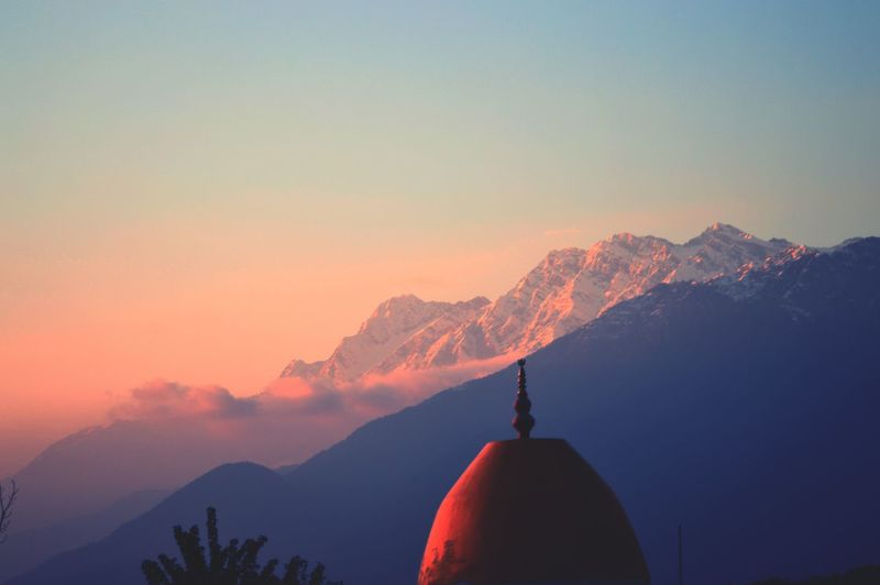 Dome of a temple with the backdrop of the himalayan ranges at sunset