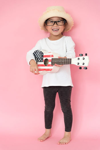 Girl playing guitar against pink background