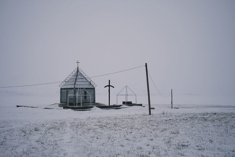 House on snow covered field against clear sky