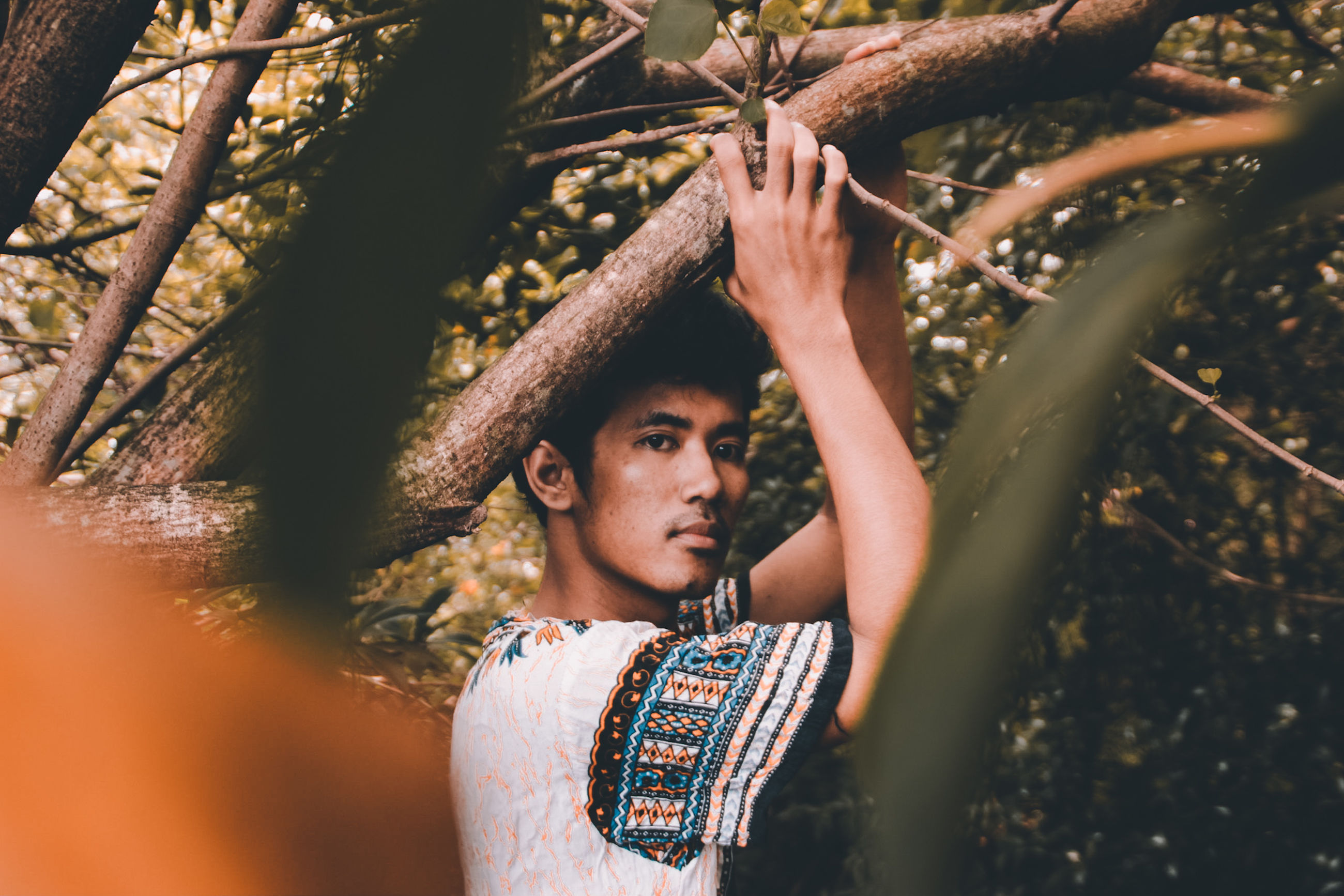 tree, real people, one person, young adult, leisure activity, lifestyles, plant, looking, day, waist up, front view, young men, casual clothing, forest, standing, nature, looking away, portrait, outdoors, human arm, arms raised, hairstyle