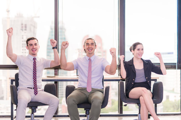 Happy Business People Celebrating Success While Siting On Chairs Against Window At Office
