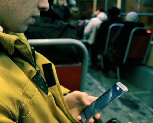 Close-up of man using mobile phone in bus