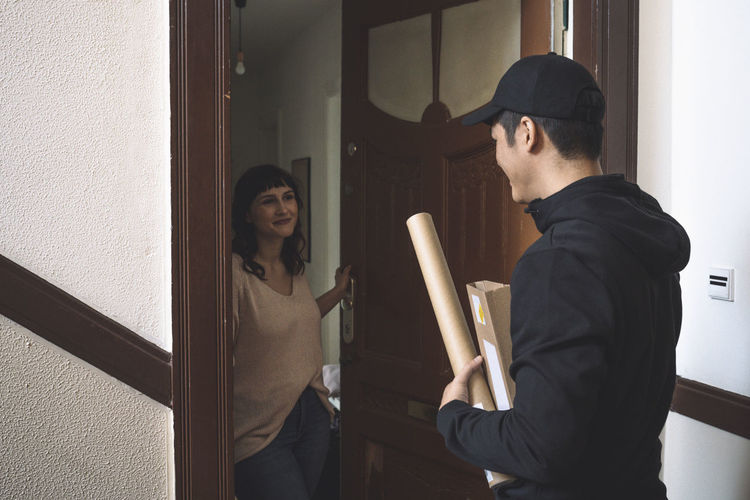 Young man and woman standing at home