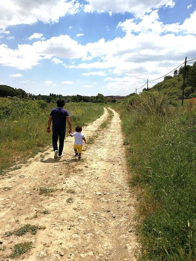 Rear view of father and son walking on dirt road amidst plants against cloudy sky