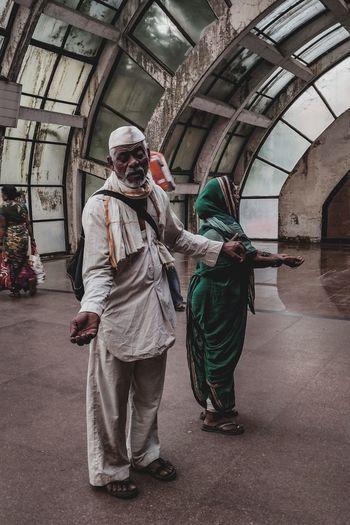 Full length of couple begging on train station