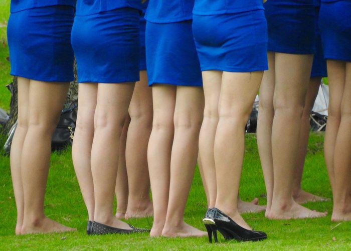 Low section of women in blue dress standing on field
