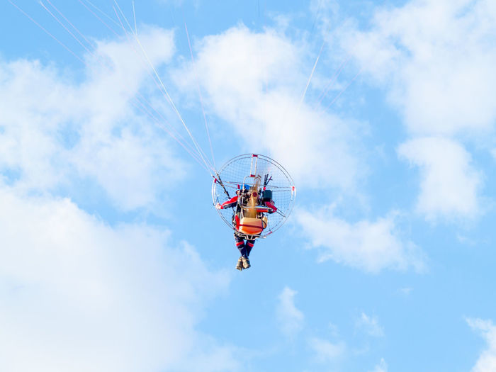 Low Angle View Of Man Paragliding Against Cloudy Sky