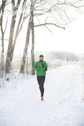 Full length of boy running on snow covered land