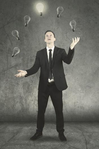 Businessman Juggling Light Bulbs Against Wall