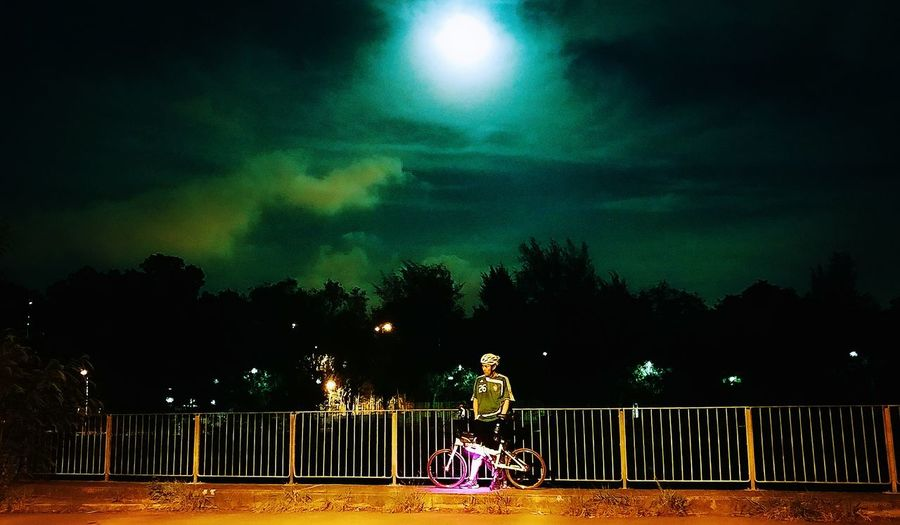 Woman sitting on railing against trees at night
