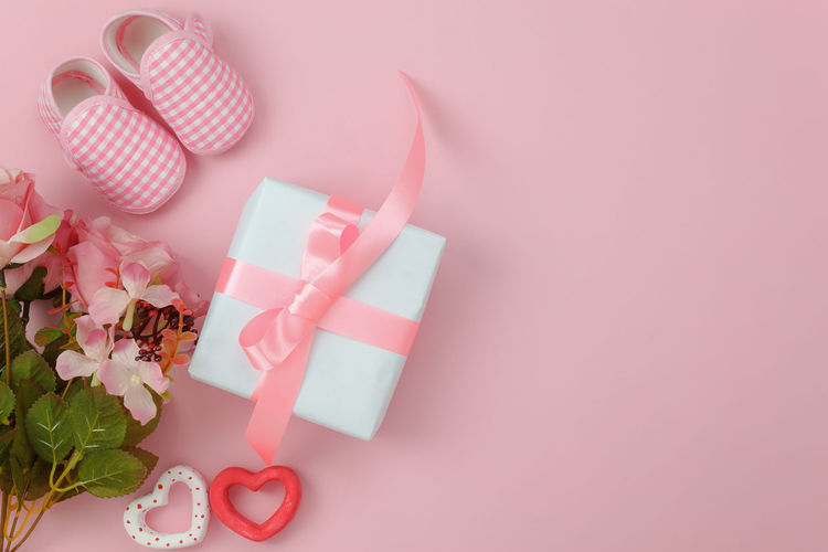 Directly above shot of gift box and shoes with flowers on pink background
