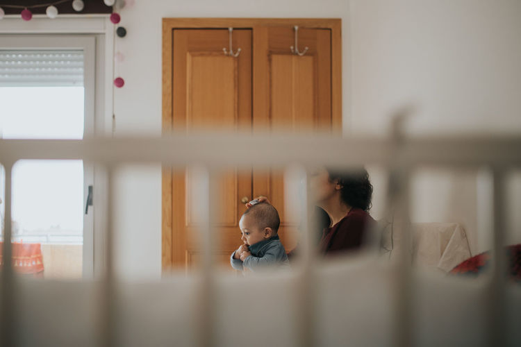 Mother with baby boy sitting at home seen through crib