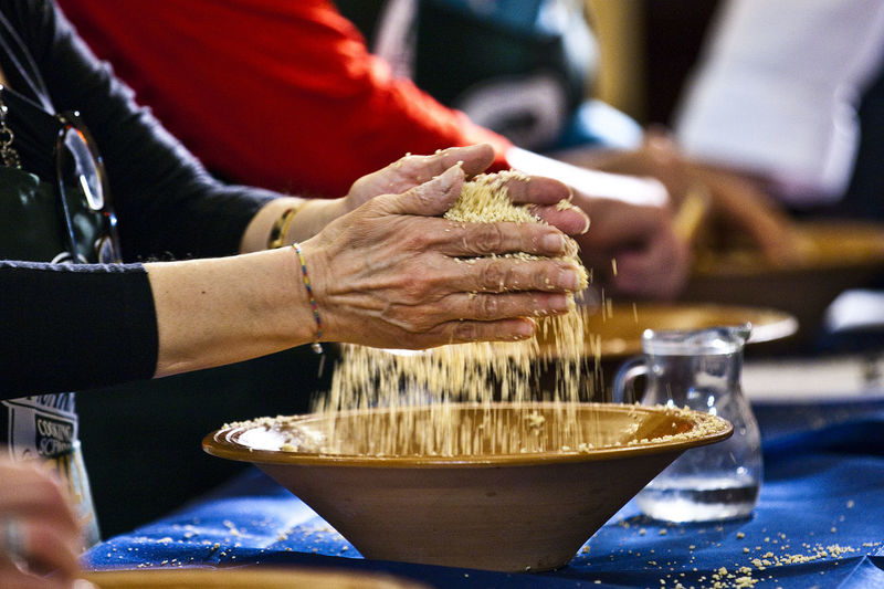 Close-up side view of hands kneading dough