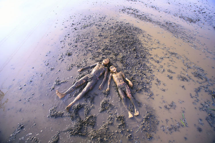 High angle view of boys lying in muddy water