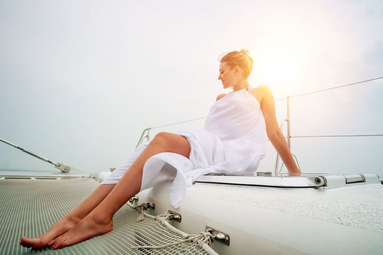 Woman sitting on boat against sky