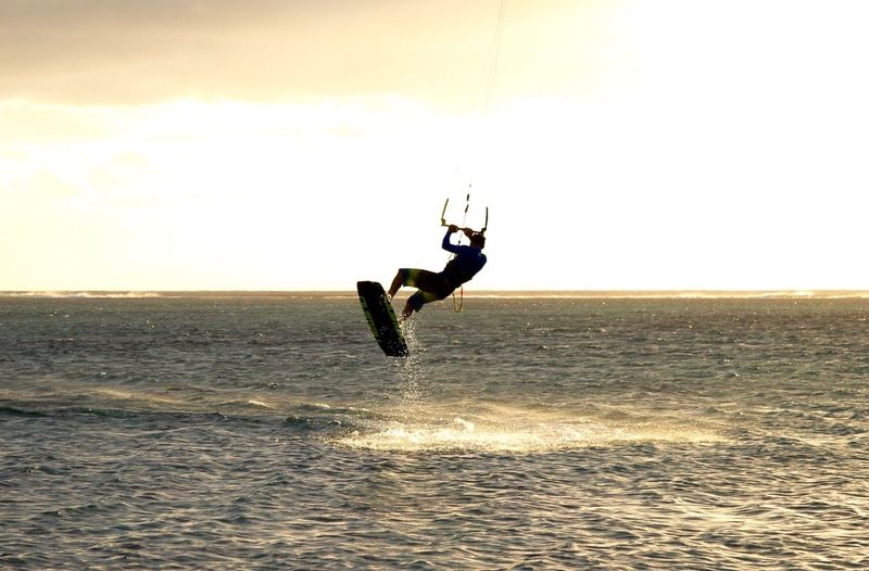 Silhouette Man Kiteboarding In Sea Against Sky During Sunset