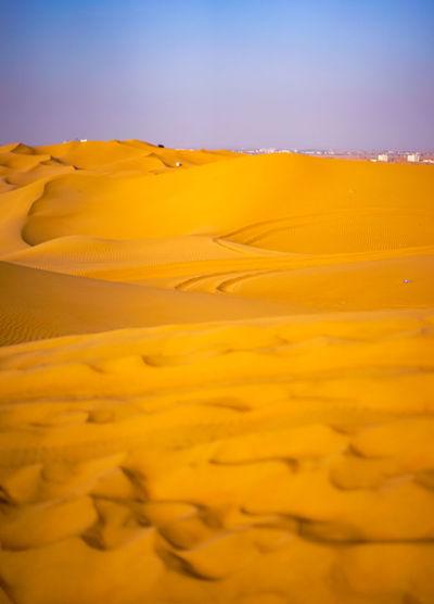 Scenic view of yellow desert against sky