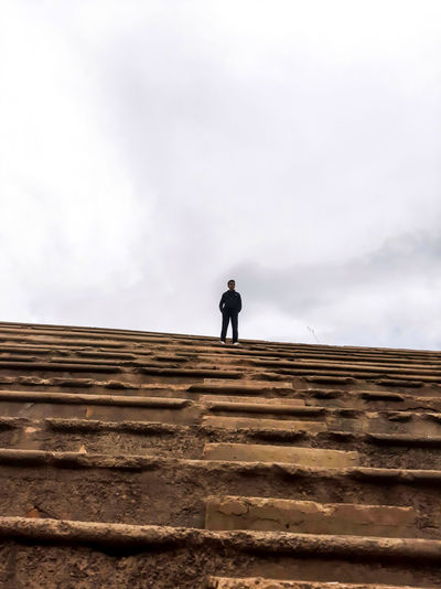 Low angle view of man standing on staircase against sky