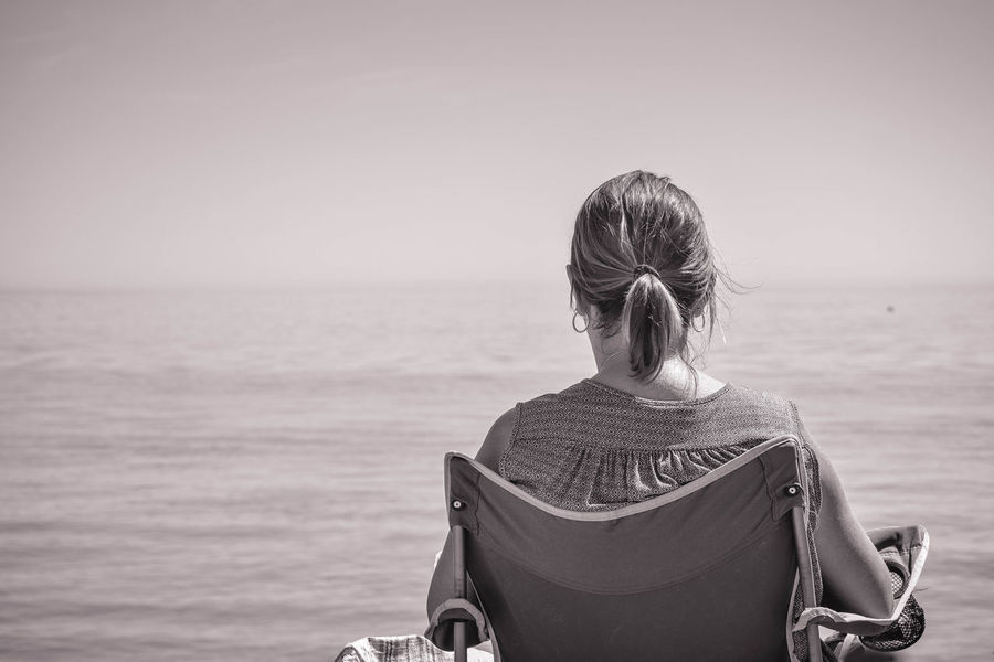 Black & White Beauty In Nature Black And White Clear Sky Day Horizon Over Water Lifestyles Looking Out To Sea Monochrome Nature One Person Outdoors Real People Rear View Rear View Of Woman Looking Out To Sea Sea Sky Space For Copy Water Woman Sitting On The Beach Women