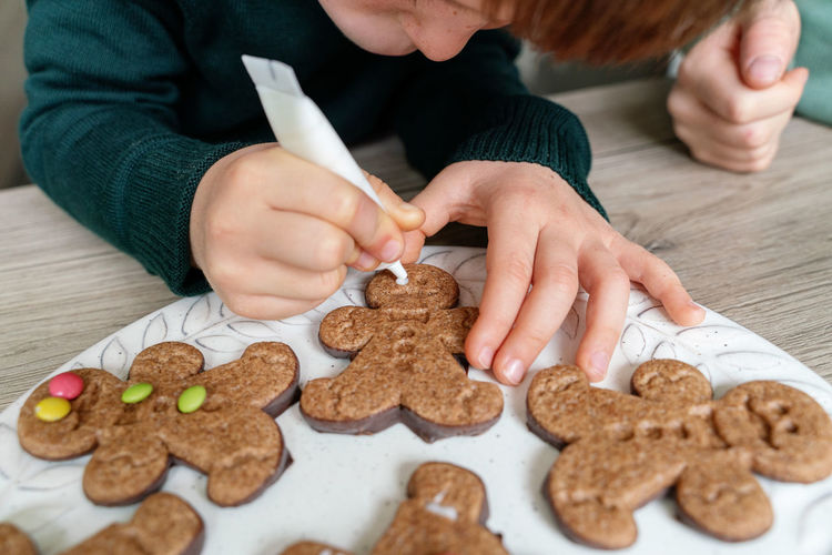 Cute boy decorating gingerbread cookies at home