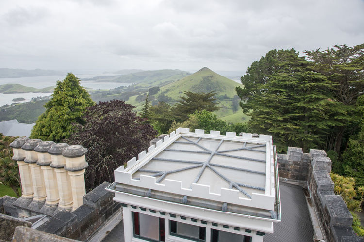 Dunedin, Otago, New Zealand-December 12,2016: Building details of Larnach Castle in Dunedin, New Zealand Castle Dunedin Mock Roof Rooftop Tourist Attraction  Architecture Beauty In Nature Building Exterior Built Structure Cloud - Sky Green Color Larnach Mountain Mountain Range Nature New Zealand Otago Outdoors Pinnacle Rainy Scenics - Nature Sky Travel Destinations Tree