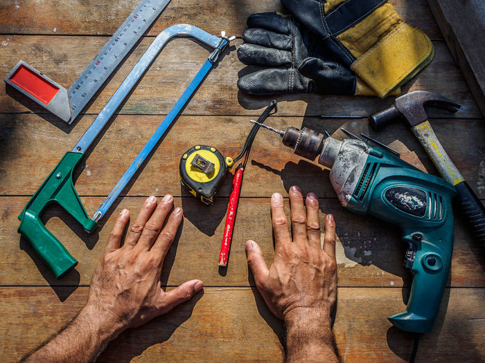 High angle view of man hands by tools on table
