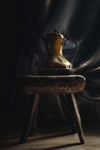 From Khoni Museum Indoors  No People Still Life Wood - Material Old Table Close-up Single Object Seat Domestic Room Metal Black Background Antique Pitcher - Jug Retro Styled Food And Drink Jug Container Dark Museum Exponat