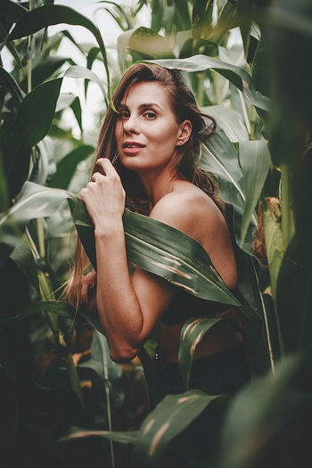 Portrait of young woman in plant