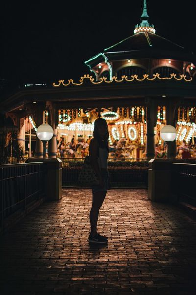 EyeEmNewHere Fun Adult Architecture Building Exterior Carousel Casual Clothing City Full Length Illuminated Leisure Activity Lifestyles Night One Person Outdoors People Real People Rear View Standing Theme Park Women Young Adult