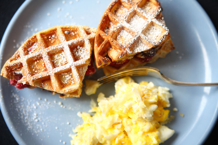 High Angle View Of Waffle Sandwich With Scrambled Eggs Served In Plate