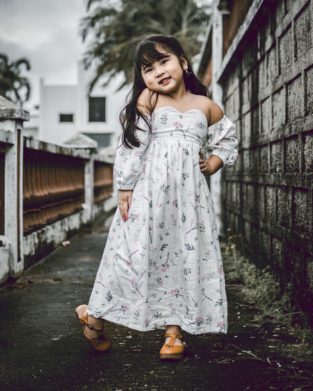 Portrait of cute girl standing on footpath