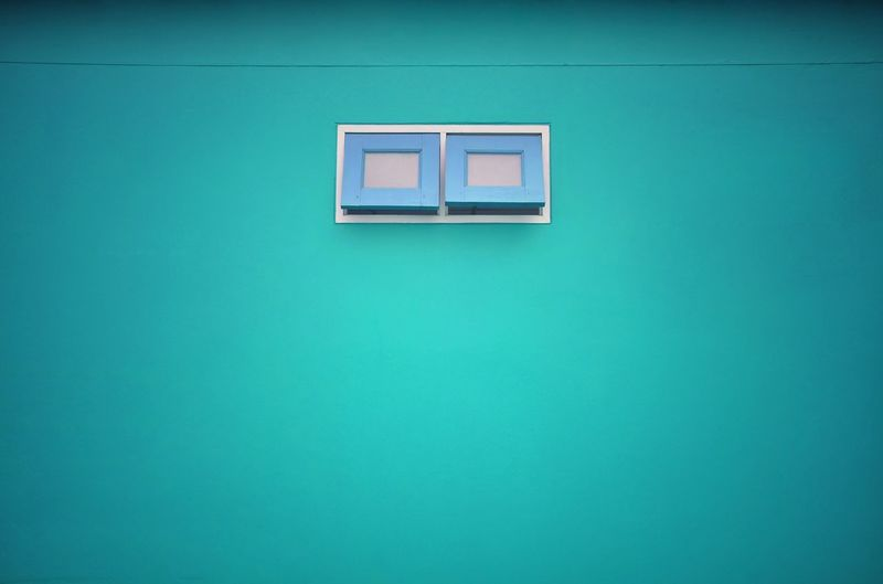Low angle view of blue window on wall of building