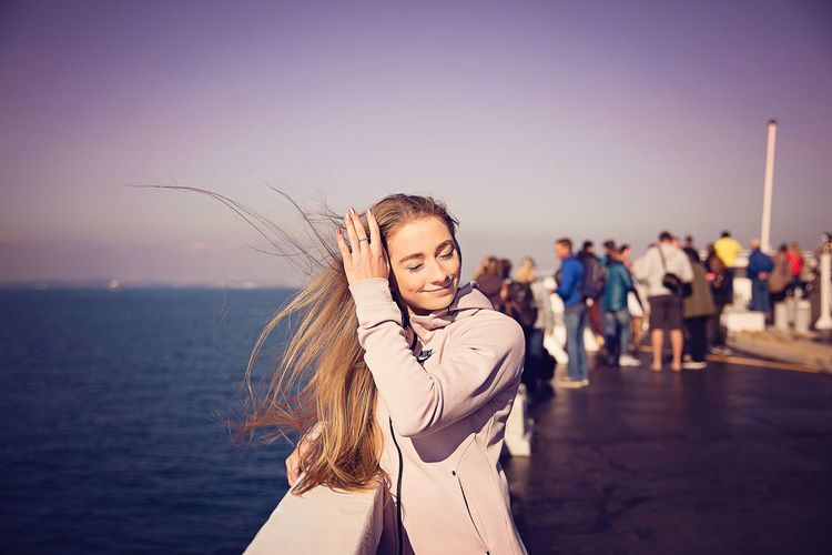 Smiling young woman with blond hair standing against sea at beach